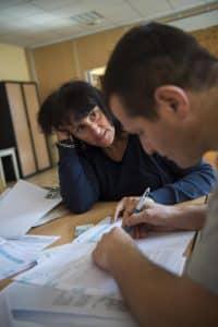 Accueil migrants et Cao d'Annecy. Benevoles et migrants préparant le dossier OFPRA.